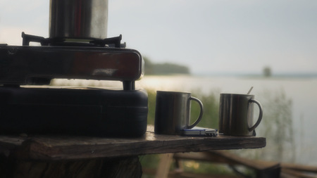 Boil in the morning on a gas stove, near a lake with beautiful sun glare on it. HD