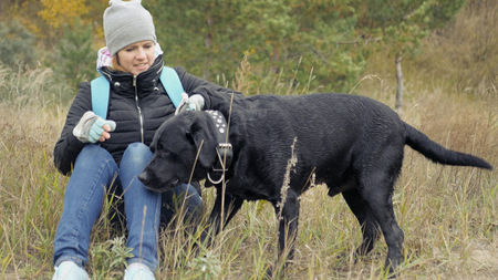 A young girl takes her dog for the collar. and wants to put her near. Photo