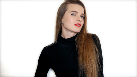 Attractive young girl with long hair and red lipstick is standing on white background and posing on camera. HD Imagens