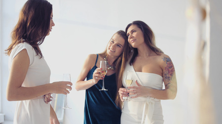 Charming girls congratulate the girlfriend, hug her, holding glasses in her hands. HD, Imagens