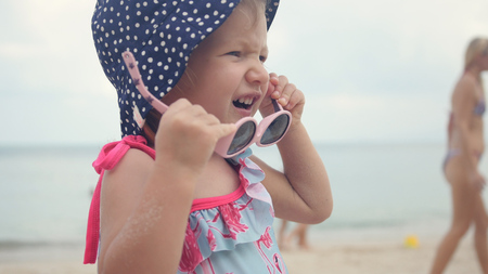 A little sweet girl in a choca in polka dots, playing with children's sunglasses.