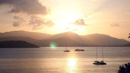 Yachts sail to the pier by the sea with a beautiful golden sunset and mountains. hd