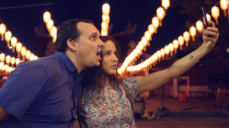 A friend is photographed on the phone at night with beautiful lanterns. The man is fooling around at the camera. HD Imagens