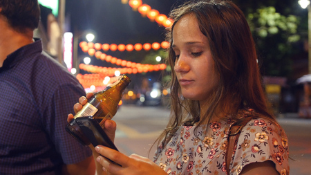 A young girl rests in the evening, drinks beer from a bottle, looks into the phone. HD 스톡 콘텐츠