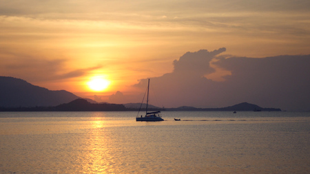 A large catamaran sails on the sea against a beautiful golden sunset. hd