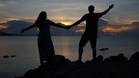A young couple holding hands, raised them upwards while admiring the magnificent sunset. HD Imagens