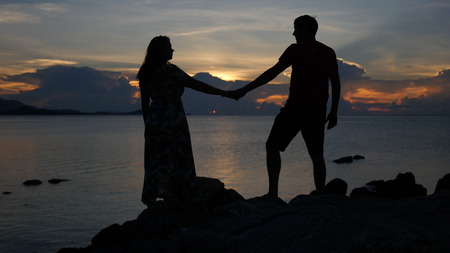 The young look at each other against the background of a magnificent golden sunset on the sea. HD