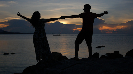 A meeting of two lovers on the beach with a beautiful sunset, holding hands, admiring the view. HD
