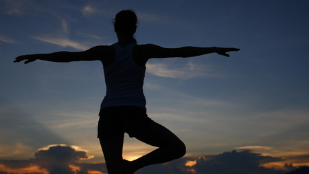A slender girl does a stance in yoga with a beautiful view of the sea and the sunset. HD