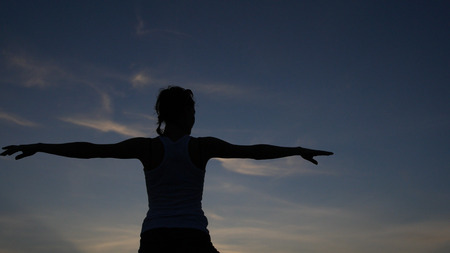 A slender girl makes a stand in yoga with a beautiful view of the sea and the sunset, observes the smoothness. HD 스톡 콘텐츠