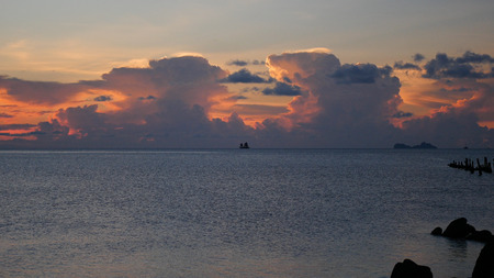 A lonely sailboat in the background of a magnificent sunset with clouds on the sea, floats along the horizon. Imagens