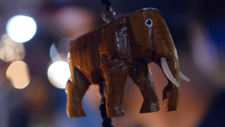 A beautiful wooden elephant weighs on the counter in the market, with a blurry background. HD,