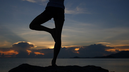 pose in yoga with a magnificent sunset at the sea. HD 스톡 콘텐츠