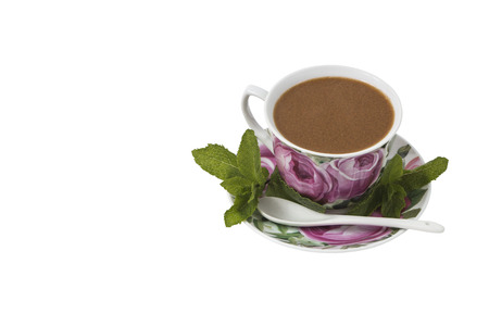 Isolated on white background Color cup of coffee on a saucer with a spoon, decorated with mint leaves. Stock Photo