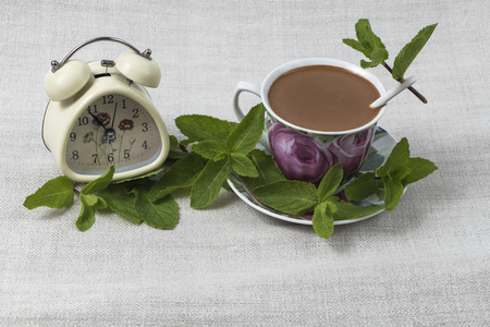 Cup of coffee with a spoon on the saucer, and an alarm clock on gray linen table cloth, decorated with green mint leaves. Stock Photo