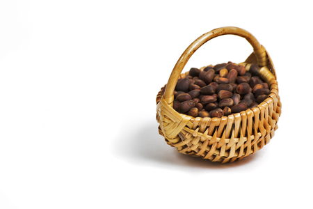 completely: Light brown wicker basket with fresh pine nuts on a completely white background with a view angle of 45 degrees.