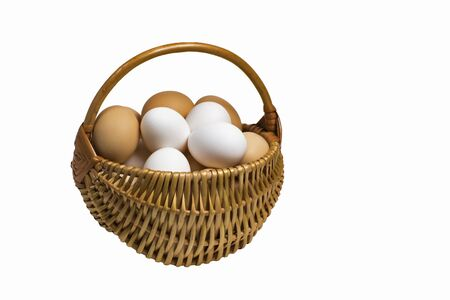 Light brown wicker basket with colorful fresh eggs isolated on a completely white background.
