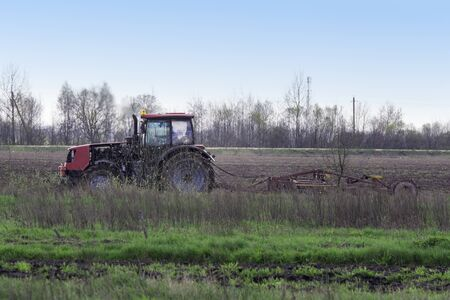 harrow: Red tractor on the background of forest and cloudy spring sky harrow handles field. Stock Photo