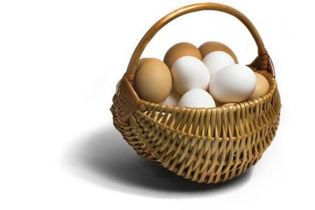completely: Light brown wicker basket with colorful fresh eggs on a completely white background with a view angle of 45 degrees.