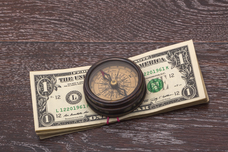 brujula antigua: Ancient compass on the background of banknotes tapered. Foto de archivo