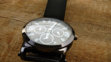 silver background: closeup hand watch on dark shed wood background Stock Photo