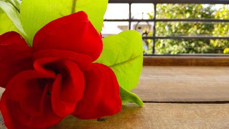Closeup künstliche rote Rose Blume mit dunklen Schuppen Hintergrund auf Holz