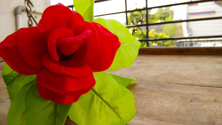 Closeup Artificial red rose flower with dark shed background on wood Фото со стока