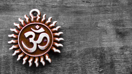 aum: om pendent on wood texture background and greeting