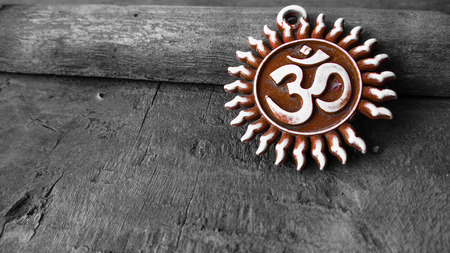 om sign: om pendent on wood texture background and greeting