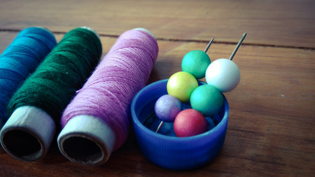 colorful sewing threads with colorful bubbles on wood background