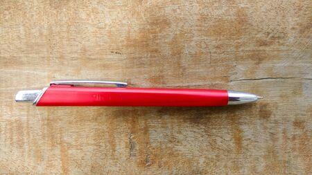 stylish red pen on wood background