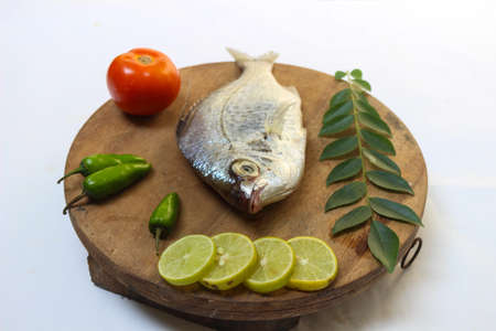 Gerres Fish (Gerres Filamentosus) / Whipfin silver biddy Fish , Decorated with curry Leaves and Tomato on a Wooden pad,White Background.