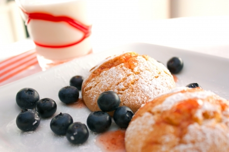 Homemade cookies for breakfast with a glass of milk and some blueberries