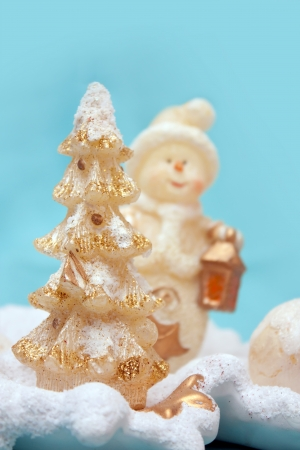 Decorative christmas tree with a snowman at the background
