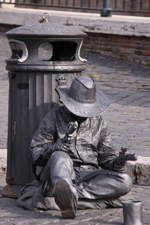 living statue of a sitting cowboy to entertain tourists in the street