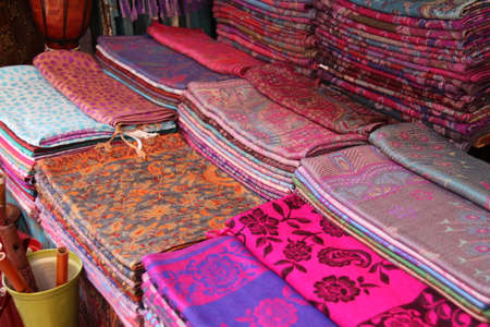 colorful display of cloth in many different colors and patterns mostly shades of pink