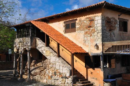 old stone house in the Spanish style with stone ladder and red roof