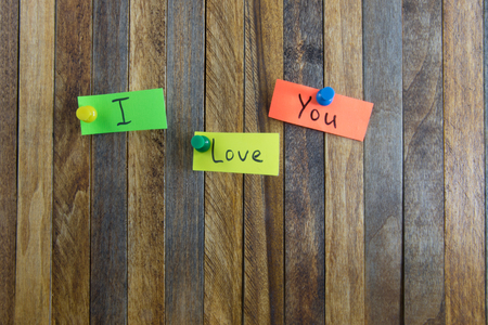 affixed: on wood background stickers affixed with the words I Love You