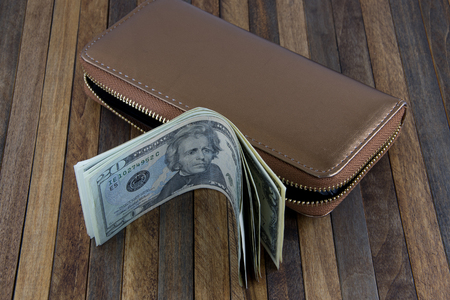 give out: Dollar banknotes ,a lot of dollars form wallet, on wooden background.