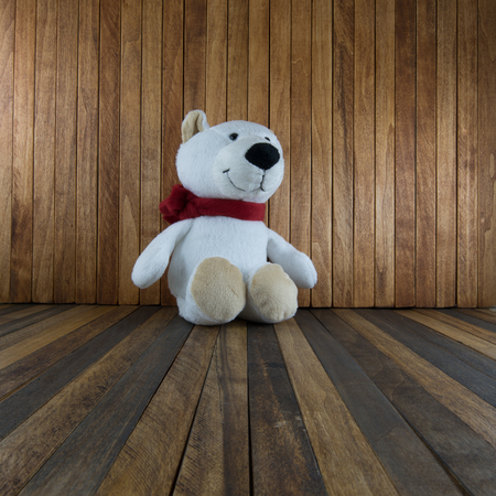 Teddy bear sitting on old wooden background. Stock Photo