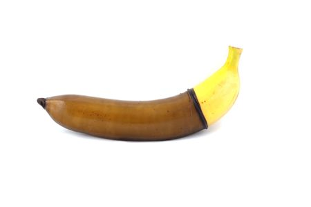 The black condom is dressed on a banana the isolated white background Stock Photo - 5566503