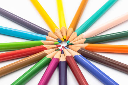 Many different color pencils lying isolated on a white background in a circle