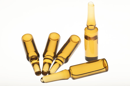 vitamine: Five brown ampoules on a white background