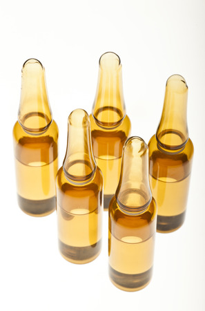 Five brown ampoules on a white background