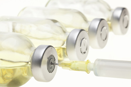 Glass Medicine Vials and Syringe on a white background Stock Photo