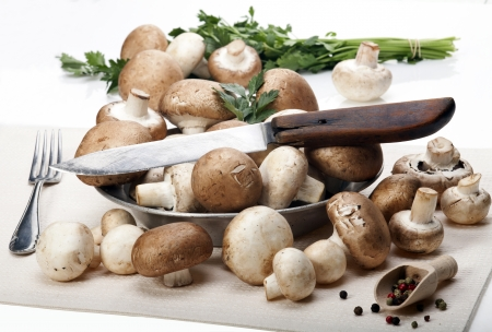 Button or Champignon and Portabello mushrooms in old metal plate with knife, fork, parsley and mixed pepper beans. On a white tablecloth. photo