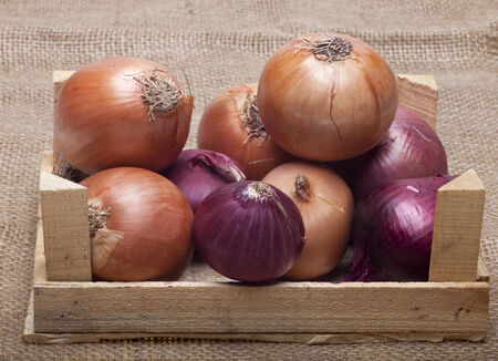 bisected: Different types of onion in a wooden crate