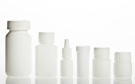 White prescription bottles with different shape on a white background photo