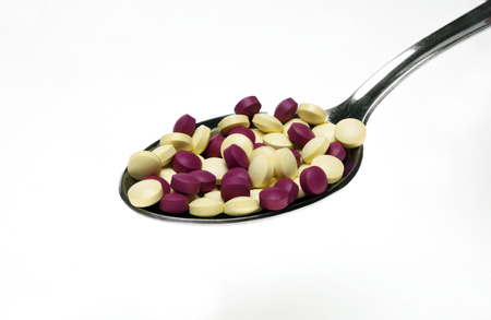 Colorful vitamin capsules on a spoon photo