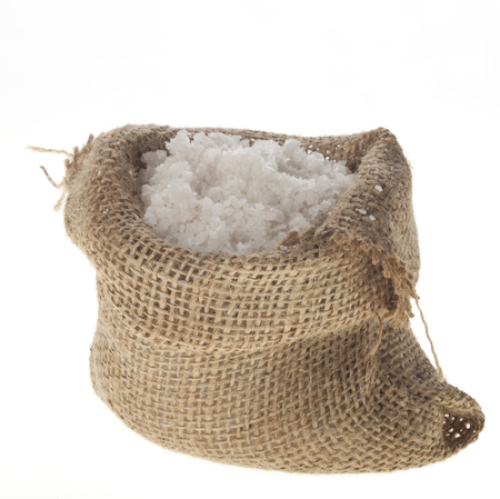 Sea salt in a jute sack on a white . photo